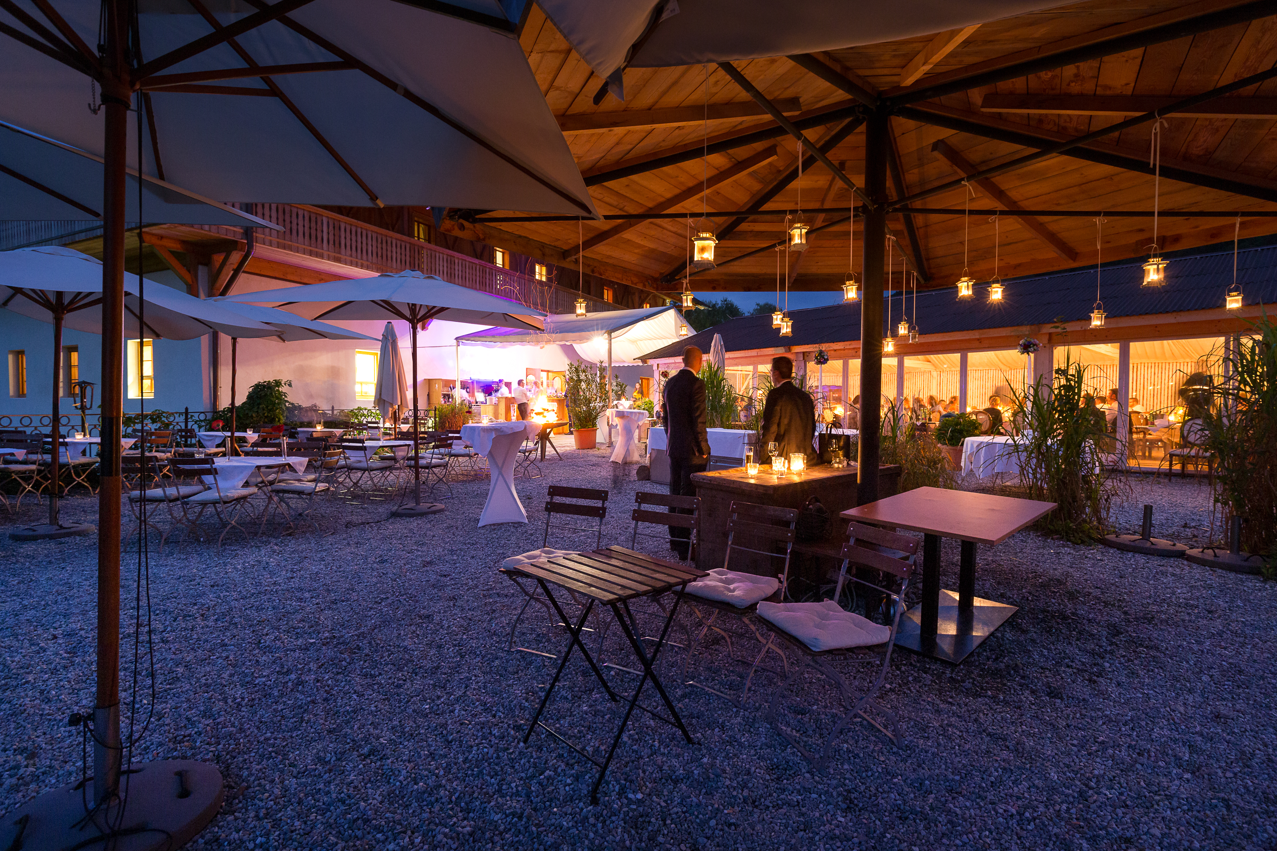 Abendliche Stimmung mit Kerzen und Lagerfeuer auf der Seeterrasse der Stiftsschmiede. Im Hintergrund der Eventpavillon.