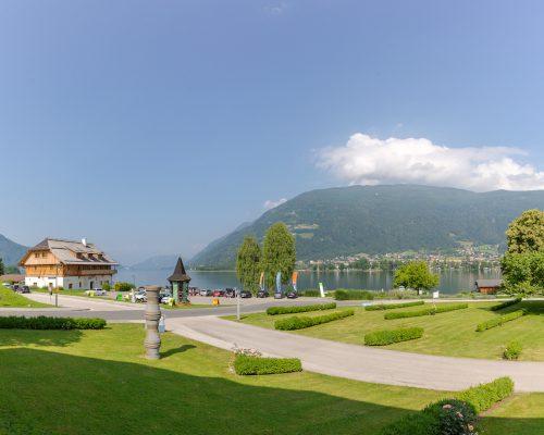 Panoramabild von Ossiach Blickrichtung Westen mit Skulpturen und grüner Wiese. Im Hintergrund die Stiftsschmiede Ossiach und der Ossiacher See.