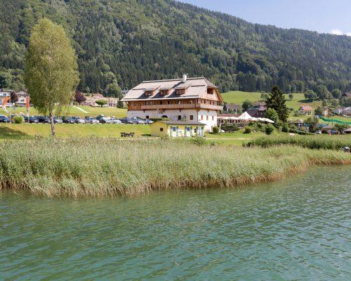 Die Stiftsschmiede Ossiach vom Ossiacher See aus gesehen. Im Vordergrund Wasser und Schilf.