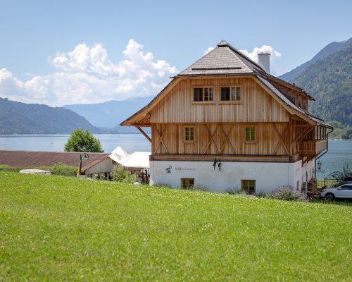 Die Stiftsschmiede in Ossiach mit saftig grüner Wiese und Ossiacher See im Hintergrund.